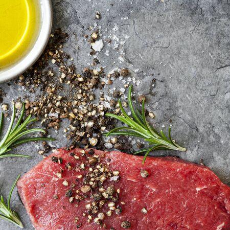seasoning: Raw beef steak with peppercorns, sea salt, olive oil and rosemary, over dark slate.  Overhead view.