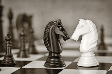 strategic planning: Chess knights head to head.  Grunge effects, monotone.
