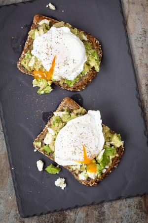 Smashed avocado and feta cheese toast with poached eggs.  Overhead view, on dark slate. Banque d'images