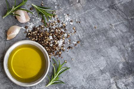 Essen Hintergrund mit Olivenöl, Pfeffer, Meersalz, Rosmarin und Knoblauchzehen, über dunklen Schiefer Hintergrund. Overhead Ansicht.