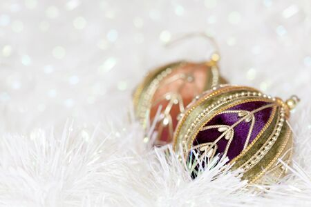 the tinsel: Christmas baubles in white tinsel, with blurred background.