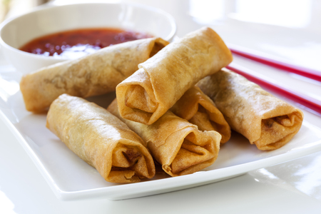 chili sauce: Spring rolls with chili sauce and chopsticks.