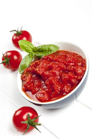 Tomato puree in bowl with cherry tomatoes and basil.