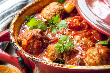 stew pot: Chicken meatballs in tomato sauce, cooking in red casserole dish. Stock Photo