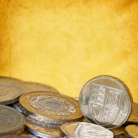 british english: British coins over grunge yellow background, with copyspace.