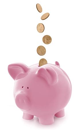 Roze spaarvarken, met dalende gouden munten. Geïsoleerd op wit. Stockfoto