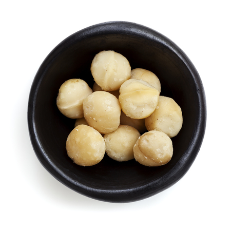 overhead view: Macadamia nuts in black bowl.  Overhead view.  Isolated on white.