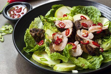 ensalada de cerdo con chile, la pera y la lechuga romana. filete a la plancha marinado en salsa de ciruela. Foto de archivo