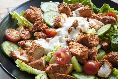 Tantoori chicken salad on black plate.