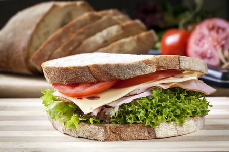 bocadillo: Emparedado de jamón con ensalada y queso. Hogaza de pan atrás.