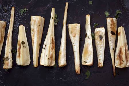 parsnips: Roasted parsnips on black slate with herbs and spices.  Overhead view.
