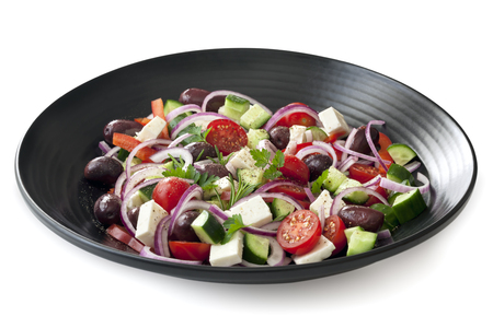 side plate: Greek salad on black plate.  Side view, isolated on white with soft shadow. Stock Photo