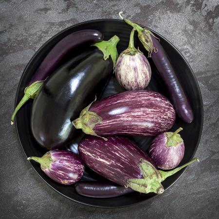 overhead view: Eggplant varieties in black bowl over dark slate background.  Overhead view. Stock Photo