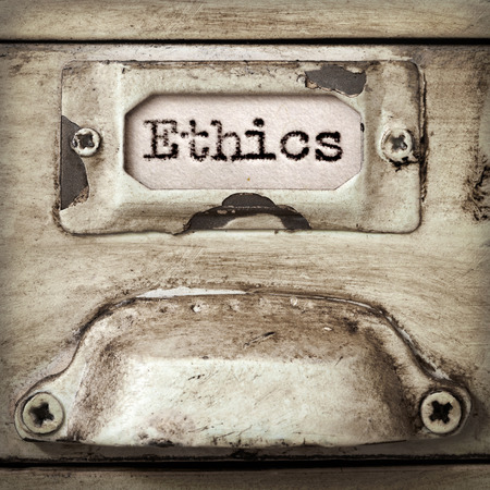 filing: Word ethics on drawer label of vintage industrial filing cabinet.