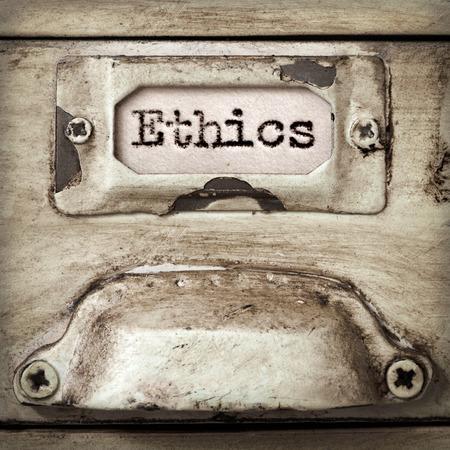 filing cabinet: Word ethics on drawer label of vintage industrial filing cabinet.