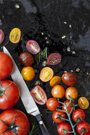 top down: Tomato varieties on black iron.  Overhead view. Stock Photo