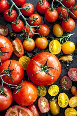 fruit background: Tomato varieties on black iron.  Overhead view. Stock Photo