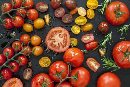 overhead view: Tomato varieties on black iron.  Overhead view. Stock Photo