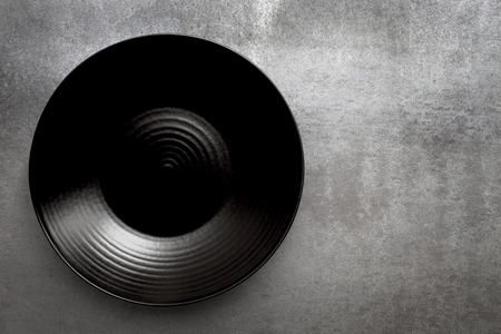 Empty round black plate over gray slate.  Aerial view, with copy space. Banque d'images