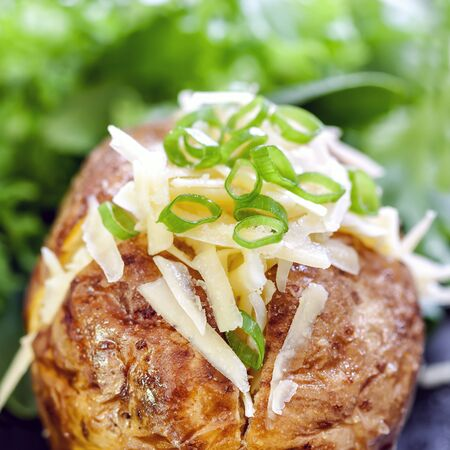 Baked potato stuffed with grated cheese and spring onion. Stock Photo