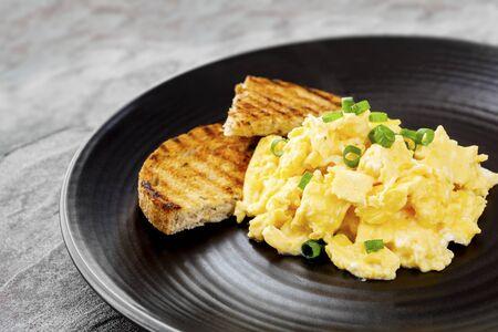 scrambled eggs: huevos revueltos con pan tostado en un plato negro.