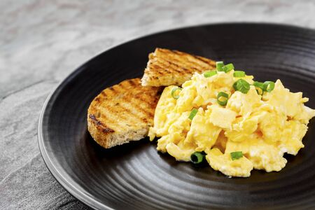 Scrambled eggs with toast on black plate. Zdjęcie Seryjne