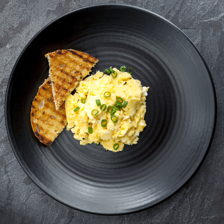 Scrambled eggs with toast on black plate. Overhead view.