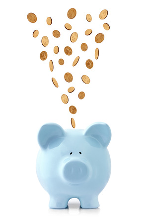 Golden coins falling into a blue piggy bank, isolated on white.  US dollar coins Banco de Imagens