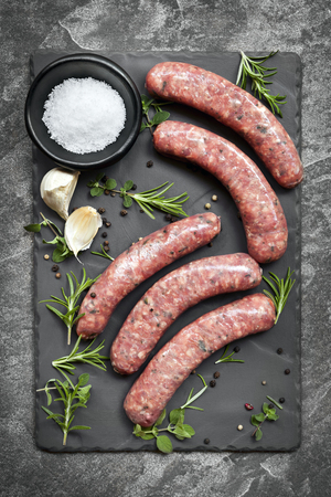 Raw sausages on slate, with herbs and spices.  Overhead view. Imagens