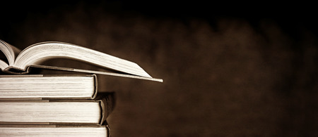 Stack of old books, with one open, over dark grunge background. Stock Photo