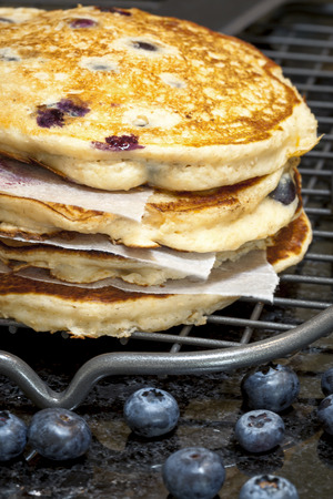 flapjacks: Stack of blueberry pancakes cooling on wire rack.