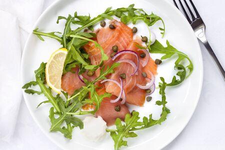 salmon ahumado: ensalada de salmón ahumado con cebolla roja, alcaparras y rúcula. Vista de arriba.