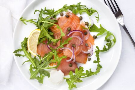 salmons: Smoked salmon salad with red onion, capers and arugula. Overhead view.