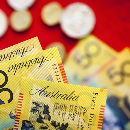 australian dollar notes: Australian fifty dollar notes over red background.  Blurred coins and notes behind. Stock Photo