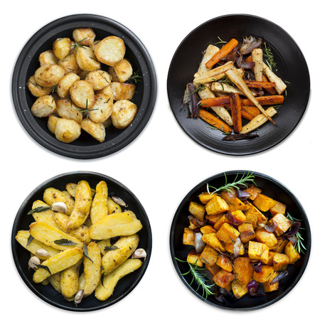 platters: Collection of roasted vegetables on black platters, isolated on white.  Includes potatoes, kumara, parsnips and carrots.