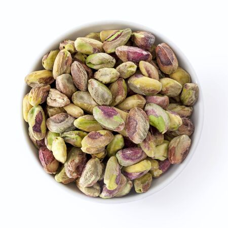 overhead view: Dish of shelled pistachio kernels isolated on white.  Overhead view.