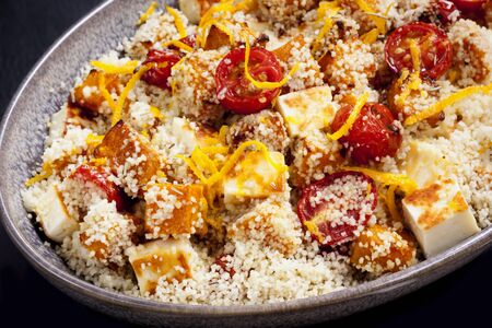 couscous: Couscous with roasted pumpkin, tomatoes and grilled halloumi cheese, topped by orange zest. Stock Photo