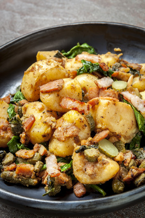 hash: Potato and spinach hash with cornichons and bacon. Stock Photo
