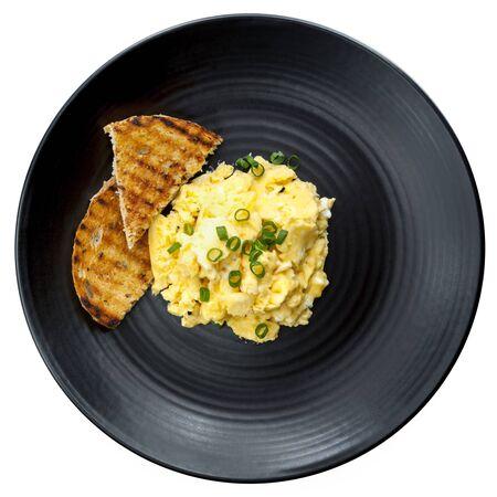 huevos revueltos: huevos revueltos con pan tostado en un plato negro. Vista superior, aislado en blanco.