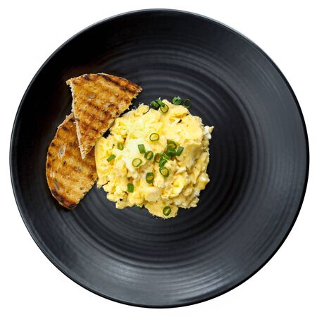 scrambled eggs: Scrambled eggs with toast on black plate. Top view, isolated on white. Stock Photo