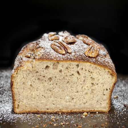 banana bread: Banana bread with pecans, straight from the oven.  Cut loaf, over black. Stock Photo