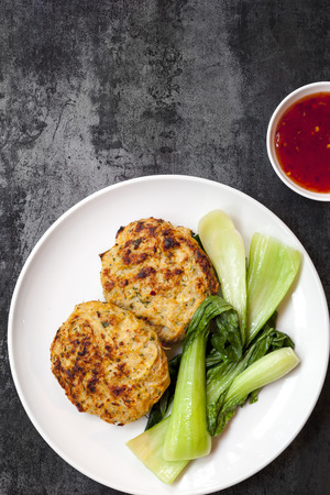chilli sauce: Thai chicken burgers with a sweet chili sauce and wilted Asian Greens.  Overhead view on slate. Stock Photo