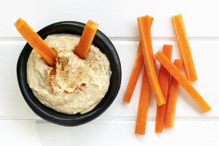 Hummus con palitos de zanahoria. Vista superior de madera sobre blanco. Foto de archivo