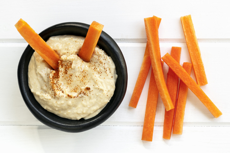 Hummus with carrot sticks.  Top view over white timber.