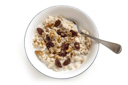oatmeal: Bowl of oatmeal with raisins, walnuts and brown sugar.  Top view, isolated on white.