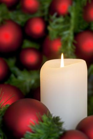 verticales: Vela de Navidad con bolas de color rojo, sobre fondo negro. Foto de archivo