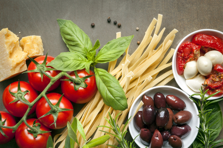 Italian food background, over slate.  Top view. Variety of ingredients, including pasta, tomatoes, basil, olives, parmesan, mozzarella, garlic, and herbs. Stock Photo