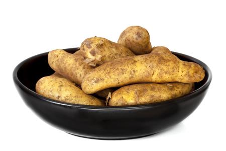 unwashed: Raw unwashed fingerling potatoes in black dish.  Isolated on white. Stock Photo