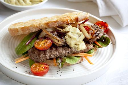 steak sandwich: Steak sandwich with salad, grilled onions and aioli.