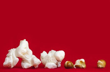 vibrant background: Popcorn over vibrant red background.  Closeup of popped and unpopped corn kernels. Side view. Very large file. Stock Photo